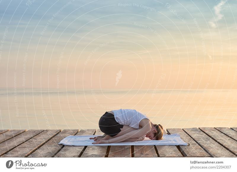 Young woman practicing yoga by sea Wellness Relaxation Meditation Vacation & Travel Summer Ocean Yoga Woman Adults Blonde Breathe Power Serene Energy conscious