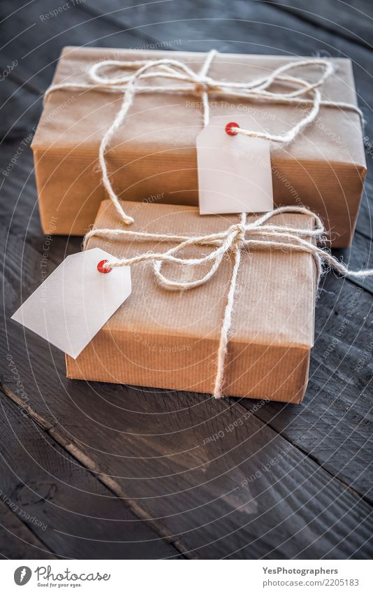 Present wrapped with brown paper and tags Feasts & Celebrations Birthday Gift String Surprise New Year's Eve Wooden table Handcrafts Festive Communication