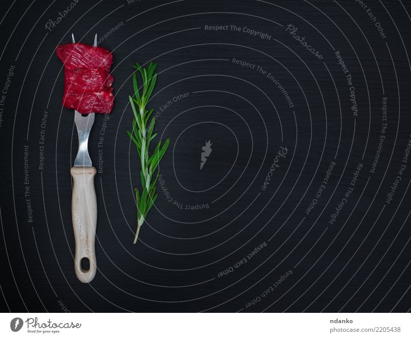 raw pieces of meat Meat Herbs and spices Dinner Cutlery Fork Table Kitchen Wood Eating Fresh Natural Green Red Black background Beef Blood board butcher Chop