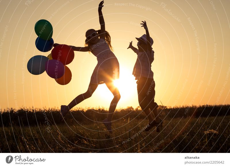 Silhouette of two happy children which playing on the field at the sunset time. They having fun on the nature. Lifestyle Joy Happy Leisure and hobbies Playing