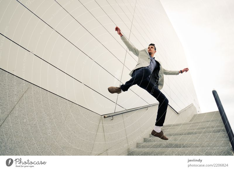 Young handsome man jumping and wearing jacket and shirt Human being Nature Man White Adults Lifestyle Style Business Fashion City life Jump Modern Stand Smiling