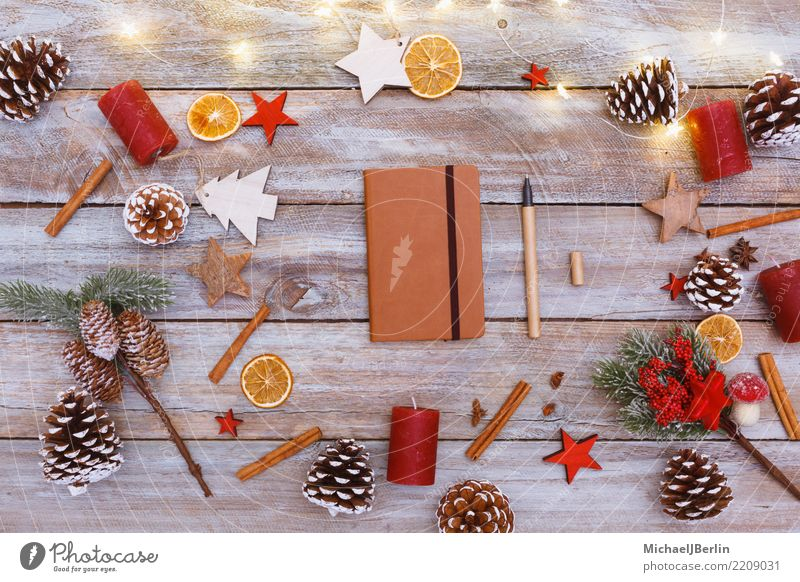 Table with Christmas decoration and notebook Winter Christmas & Advent Write Chaos Arranged Reindeer Notebook Pen December Light Decoration Fir cone Wood Paper