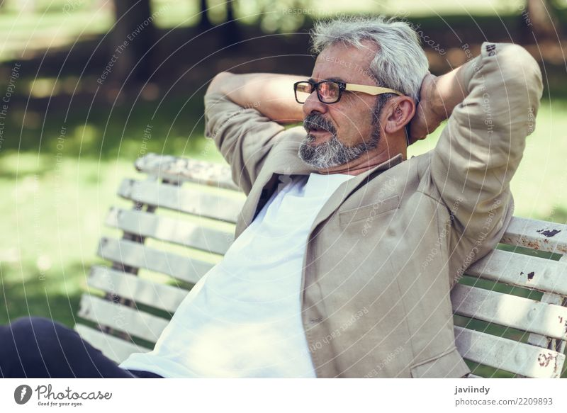 Pensive mature man sitting on a bench in an urban park Lifestyle Happy Retirement Human being Masculine Man Adults Male senior 1 45 - 60 years