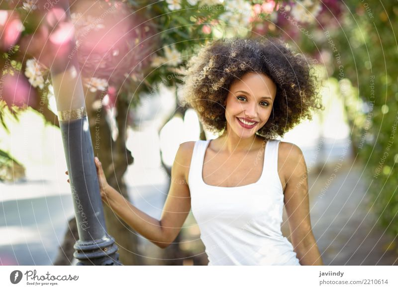 Mixed female with afro hairstyle smiling in urban park. Lifestyle Style Happy Beautiful Hair and hairstyles Face Summer Human being Feminine Young woman