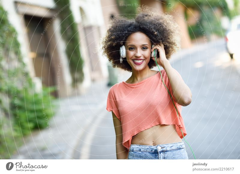 Portrait of young attractive black girl in urban background listening to the music with headphones. Lifestyle Joy Happy Beautiful Hair and hairstyles Face