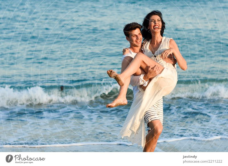Young happy couple walking in a beautiful beach. Lifestyle Joy Happy Beautiful Hair and hairstyles Vacation & Travel Summer Beach Ocean Human being Woman Adults