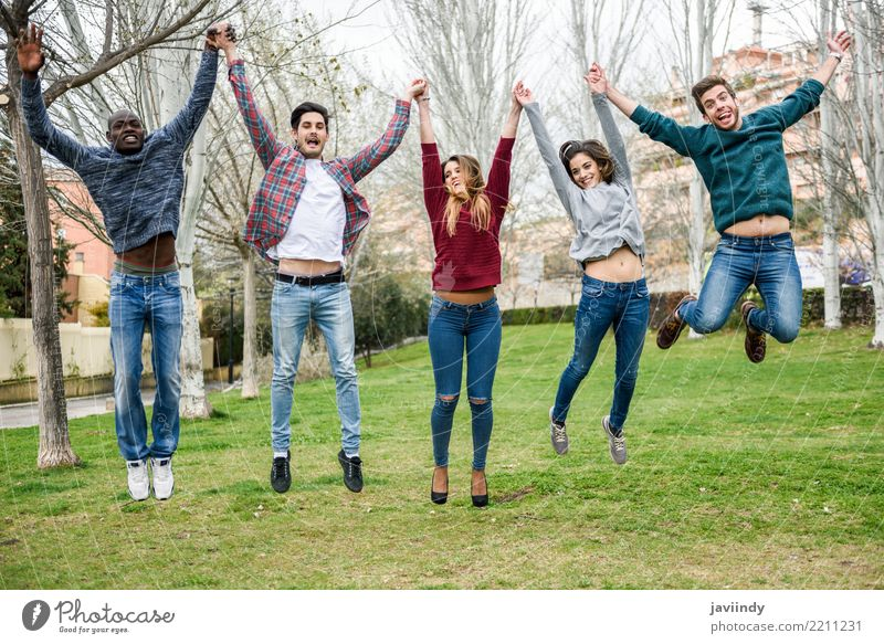 Multiracial young people jumping together outdoors Lifestyle Joy Human being Woman Adults Man Friendship 5 Group 18 - 30 years Youth (Young adults) Park Street
