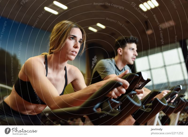 Couple in a spinning class wearing sportswear. Cyclo indoor. Woman Human being Youth (Young adults) Man 18 - 30 years Adults Lifestyle Feminine Sports Group