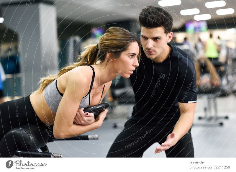 Personal trainer helping young woman lift weights Lifestyle Body Sports Human being Masculine Woman Adults Man 2 18 - 30 years Youth (Young adults) Railroad