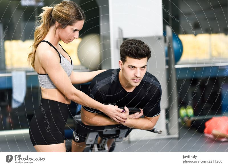 Female personal trainer helping a young man Woman Human being Youth (Young adults) Man White 18 - 30 years Adults Lifestyle Feminine Sports Masculine Body Power