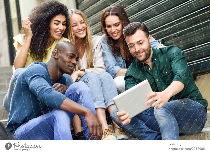 Multiracial group looking at a tablet computer outdoors Woman Human being Youth (Young adults) Man Beautiful Joy 18 - 30 years Adults Street Lifestyle Feminine