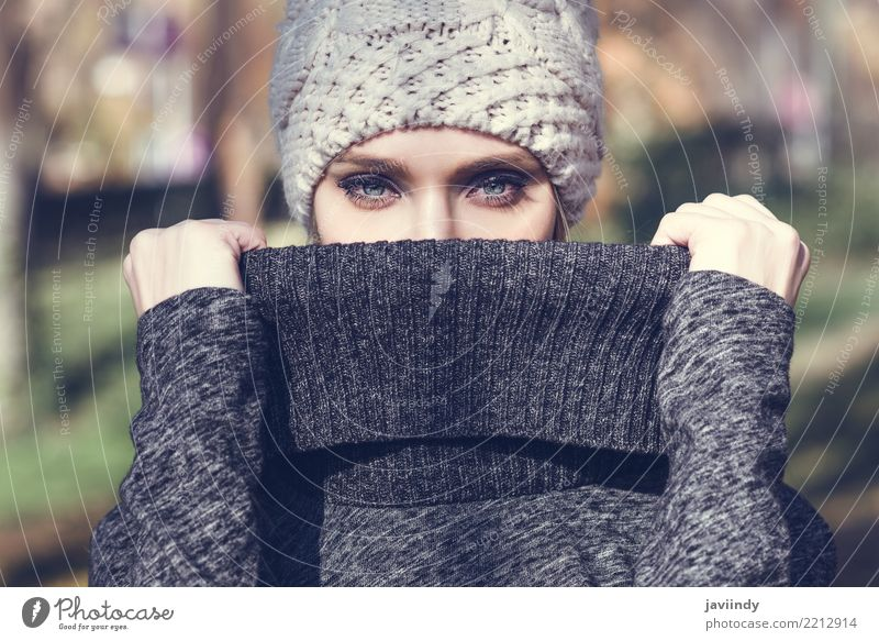 Woman standing in a park with winter wool cap Human being Blue Beautiful White Winter Adults Street Lifestyle Autumn Feminine Style Hair and hairstyles Fashion