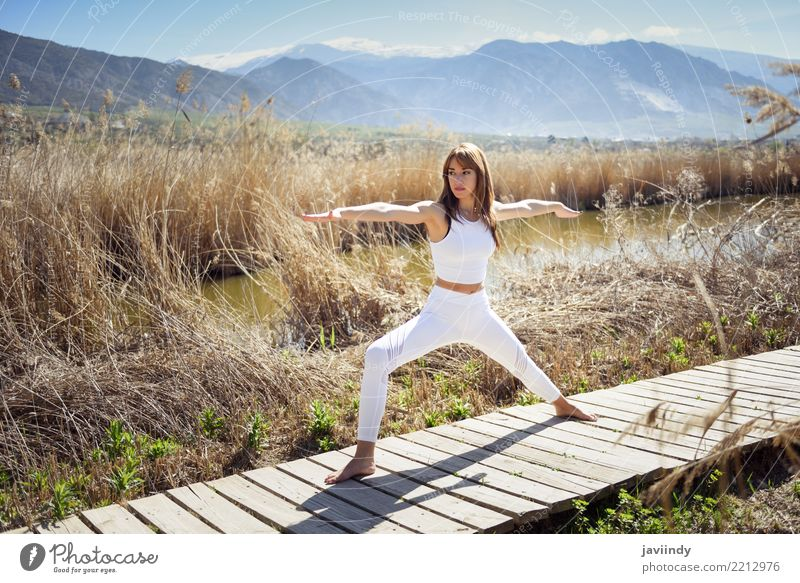 Young woman doing yoga in Nature. Lifestyle Beautiful Wellness Relaxation Meditation Summer Sports Yoga Human being Woman Adults Fitness Thin White Warrior pose