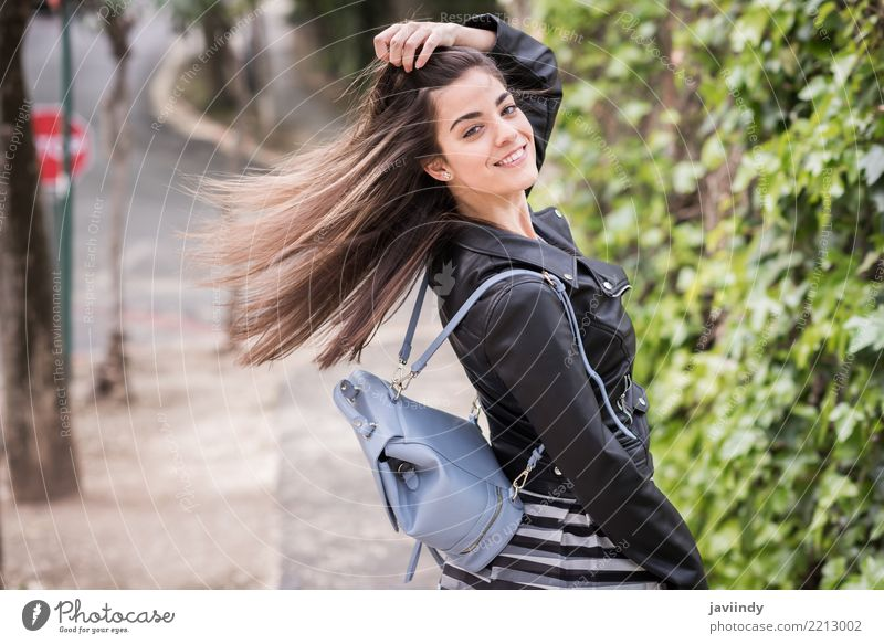 Young woman moving her hair in urban background Lifestyle Style Happy Beautiful Hair and hairstyles Human being Woman Adults Wind Street Fashion Skirt Jacket