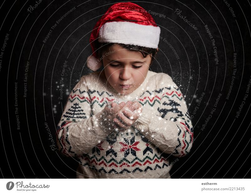 little child blows snow from hands in christmas Lifestyle Vacation & Travel Adventure Winter Party Event Feasts & Celebrations Christmas & Advent New Year's Eve