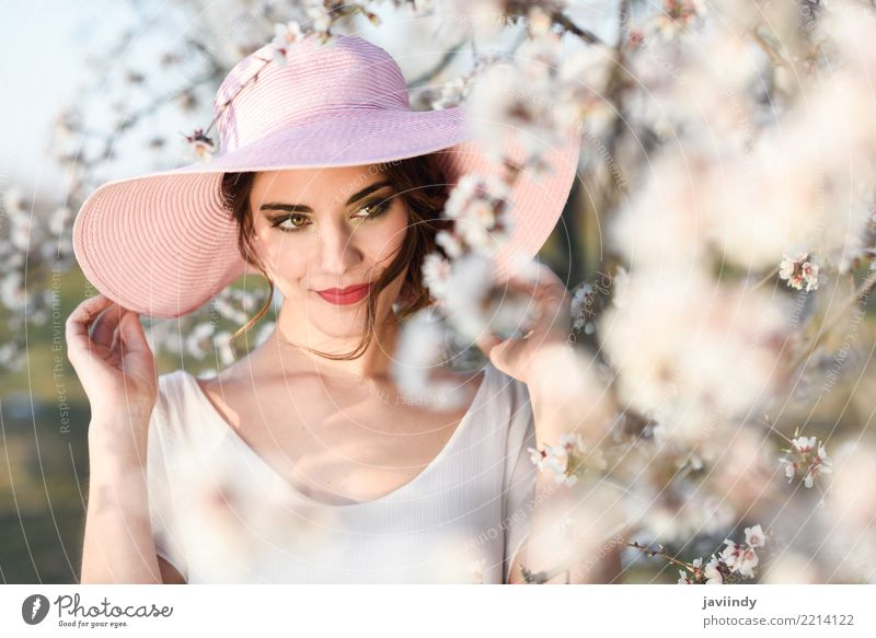 Woman in the flowered field in the spring time Style Happy Beautiful Face Human being Adults Nature Tree Flower Blossom Park Fashion Dress Hat Brunette Pink