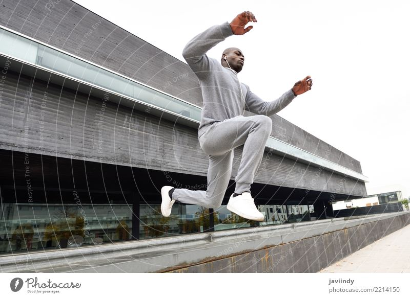 Black man jumping in urban background. Lifestyle Sports Jogging Human being Man Adults Street Fitness Jump running african movement forward young action health