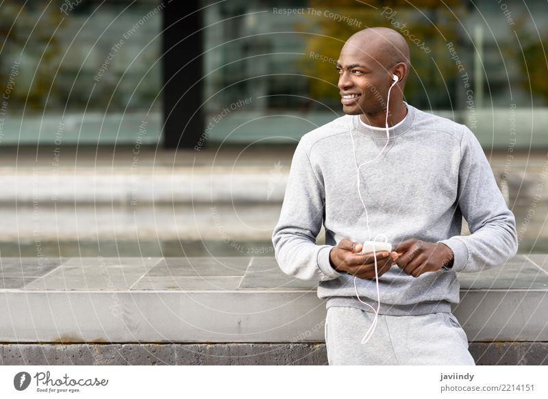 Attractive black man listening to music with headphones Lifestyle Happy Music Sports Telephone PDA Technology Human being Man Adults 1 18 - 30 years