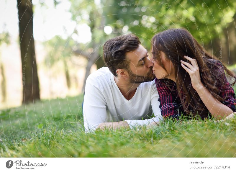 Beautiful young couple kissing on grass in an urban park Woman Nature Youth (Young adults) Man Summer Green Joy 18 - 30 years Adults Lifestyle Autumn Love Grass