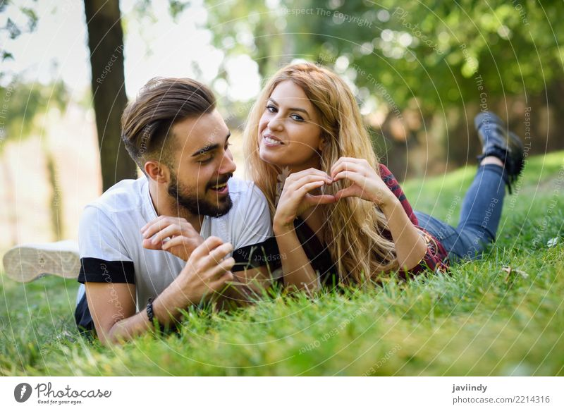 Beautiful young couple laying on grass in an urban park. Woman Human being Nature Youth (Young adults) Man Summer Green Joy 18 - 30 years Adults Lifestyle