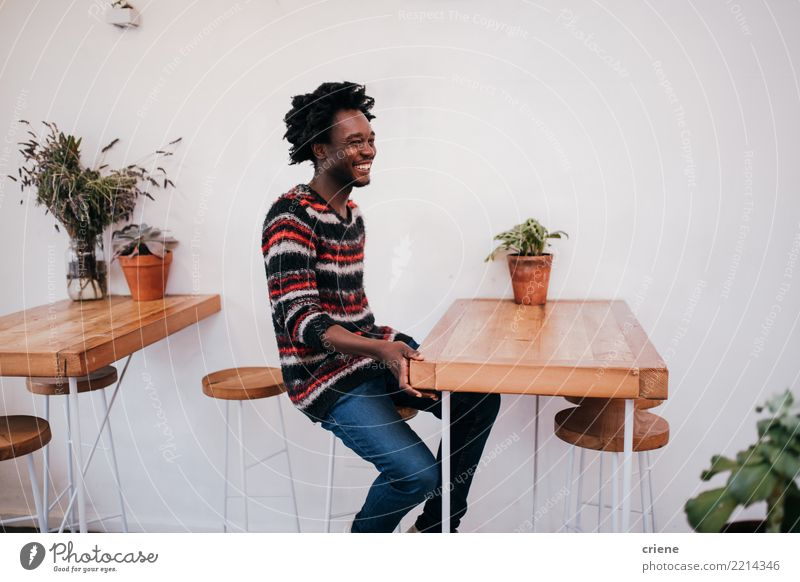 Young happy afro american man sitting in cafe Lifestyle Joy Relaxation Table Restaurant Human being Man Adults Youth (Young adults) Afro Wood Smiling Sit Modern