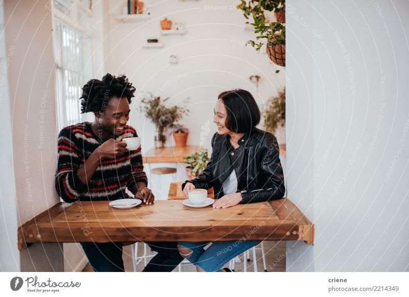 Mixed Race young adult couple drinkin coffee in cafe Human being Youth (Young adults) Young woman Young man Joy 18 - 30 years Adults Lifestyle Love Emotions