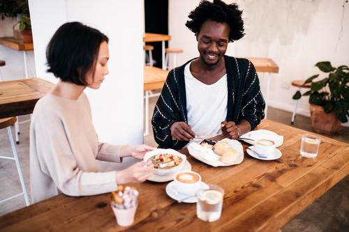Mixed Race couple eating breakfast together in restaurant Human being Youth (Young adults) Young woman Young man Relaxation Joy 18 - 30 years Adults Eating