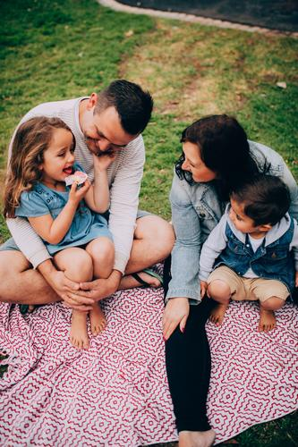 Young family having quality time at he park together Child Woman Nature Vacation & Travel Man Relaxation Joy Adults Lifestyle Love Meadow Grass Laughter