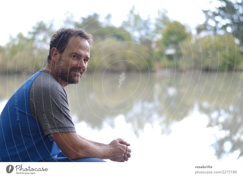 middle-aged dark-haired man with beard squats in a clearing by the pond and looks over his shoulder into the camera Leisure and hobbies Human being Man Adults 1