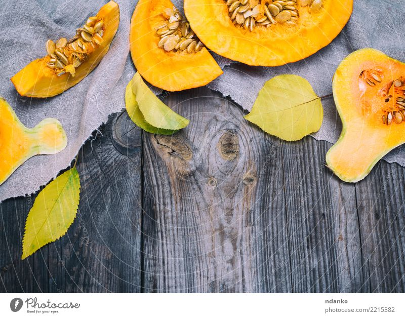 half a fresh pumpkin Vegetable Eating Dinner Organic produce Vegetarian diet Table Hallowe'en Autumn Wood Fresh Above Yellow Gray Tradition Pumpkin food healthy