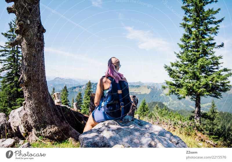 Young woman takes a break in the Alps Hiking Nature Landscape Summer Beautiful weather Tree Bushes Rock Mountain Sunglasses Backpack Blonde Cow Think To enjoy