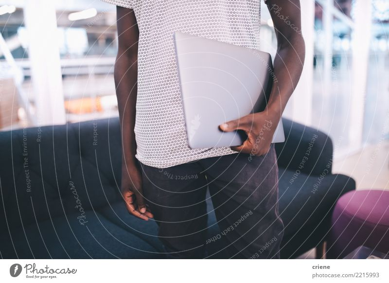 Young adult holding laptop in office Man Adults Business Work and employment Office Technology Success Driving Digital Businessman Hold Afro African-American