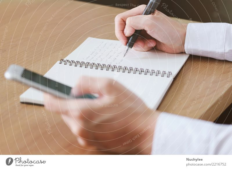 hand writing on notebook with using smartphone Work and employment Office Business Telephone Cellphone PDA Screen Internet Woman Adults Man Hand Media Paper Pen