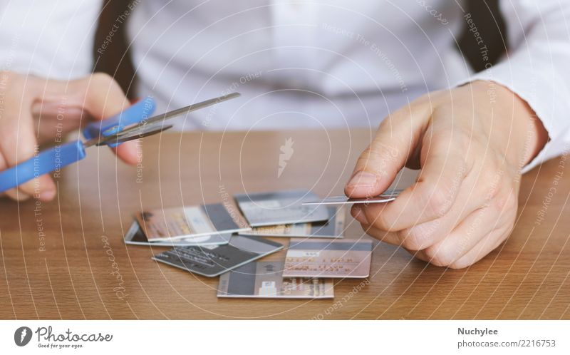 Hand cutting credit card with scissors on table Table Economy Financial Industry Financial institution Scissors Woman Adults Man Fingers Plastic Poverty Safety