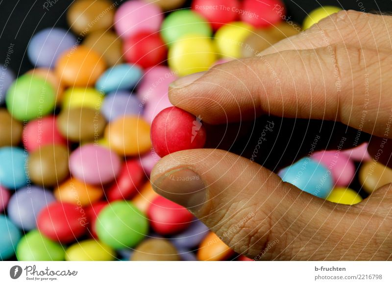 The Red Candy Healthy Alternative medicine Man Adults Hand Fingers To hold on Multicoloured Chocolate buttons Pill Addiction Take Select Selection Colour photo