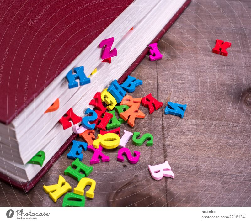 wooden letters fall out of a closed book Table Book Wood Reading Blue Brown Pink Red Idea Study School Information colorful cover alphabet knowledge