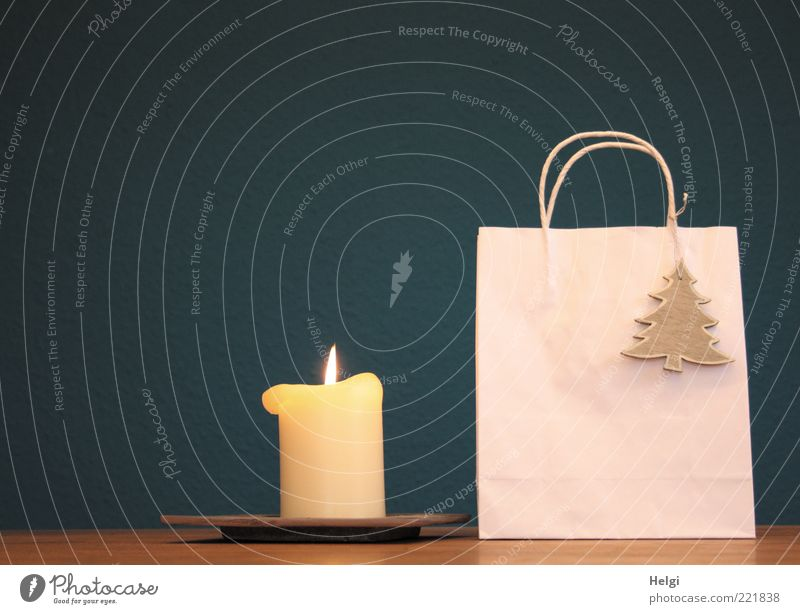 Paper bag with wooden fir tree as decoration and burning candle standing on a table in front of a dark blue background Design Decoration Packaging