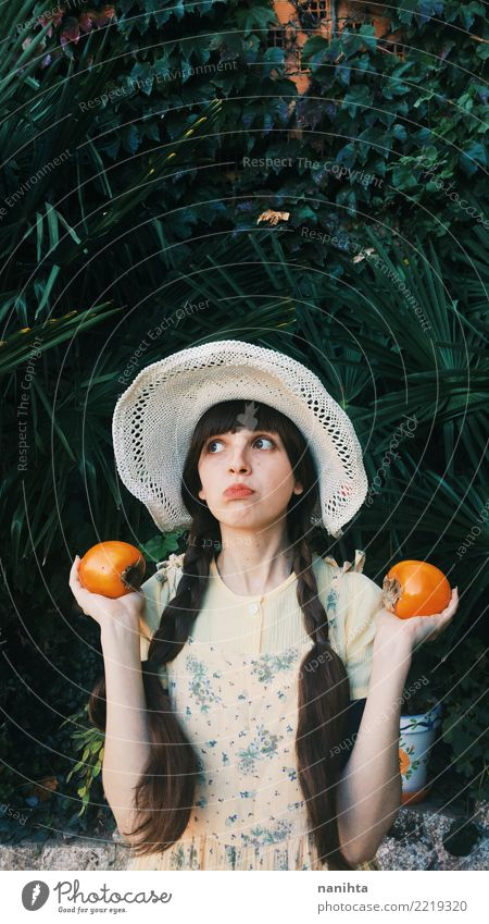 Young retro woman holding persimmons Human being Nature Youth (Young adults) Young woman Beautiful Green White 18 - 30 years Adults Environment Healthy Funny