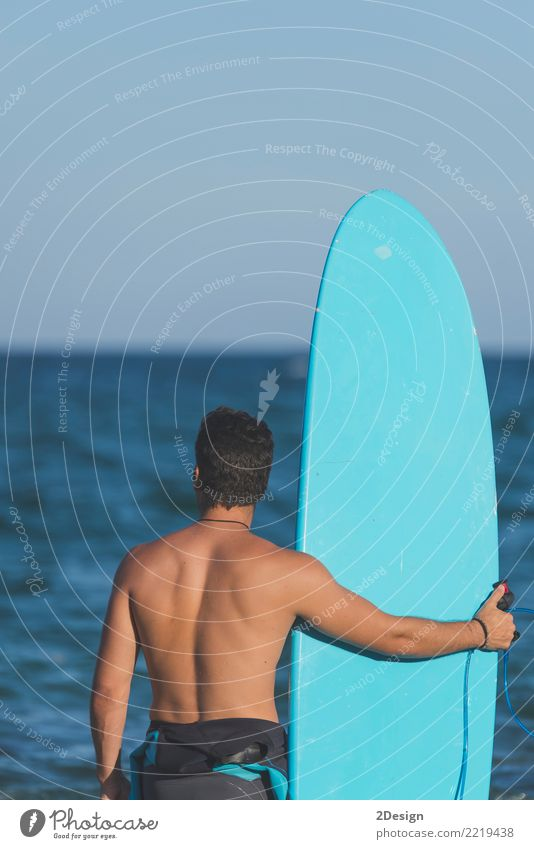Surfer holding his surfboard at the beach Lifestyle Joy Vacation & Travel Summer Beach Ocean Waves Sports Man Adults Youth (Young adults) Sky Clouds Coast