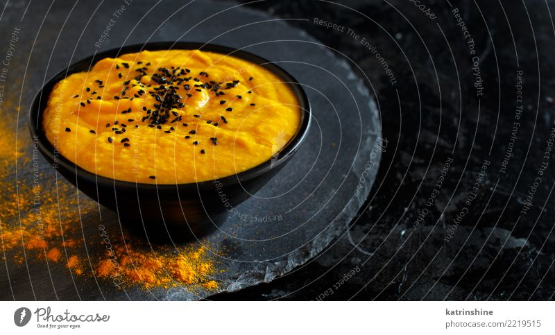Fresh pumpkin soup in a bowl on a dark background Vegetable Soup Stew Vegetarian diet Bowl Thanksgiving Hallowe'en Autumn Dark Delicious Yellow Black Colour