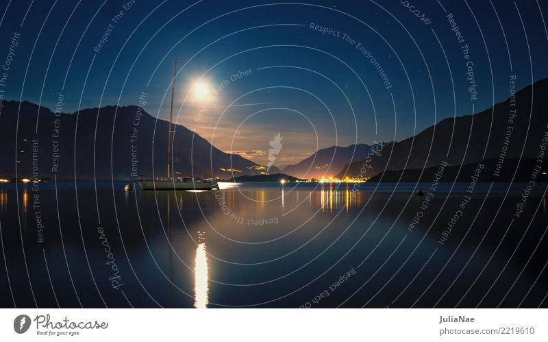 View of Lake Como at night Calm Mountain Water Moon Sailboat Watercraft Dark Moonlight Lago di Como Italy Lombardy Italian Mediterranean Lighting rays