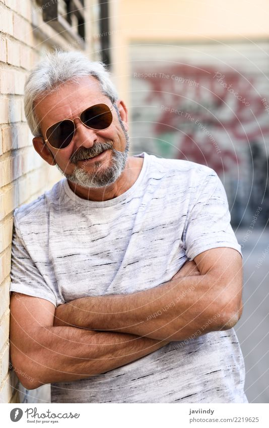 Mature man smiling at camera in urban background Human being Man Old White Adults Street Lifestyle Happy 45 - 60 years Smiling Clothing Male senior Sunglasses