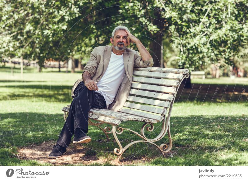 Pensive mature man sitting on a bench in an urban park. Lifestyle Happy Retirement Human being Man Adults Male senior 1 45 - 60 years Park Street Clothing Beard