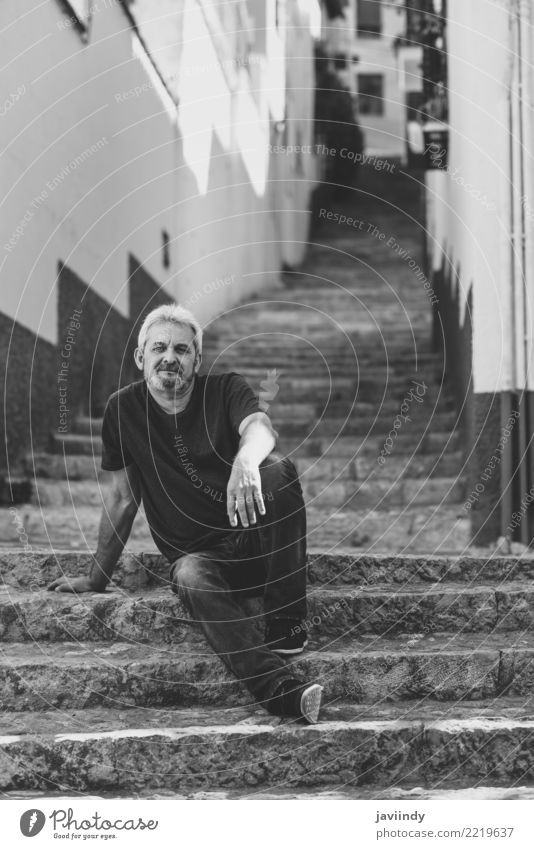 Portrait of a mature man sitting on steps in the street. Human being Man Old White Adults Street Lifestyle Happy Masculine 45 - 60 years Smiling Clothing