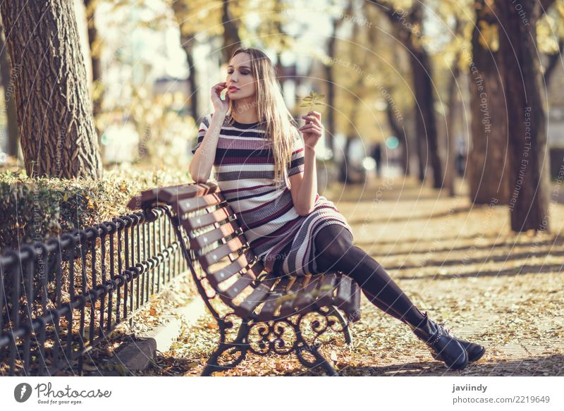 Young blonde woman sitting on a bench in the street Woman Human being Youth (Young adults) Young woman Beautiful White Leaf 18 - 30 years Adults Street
