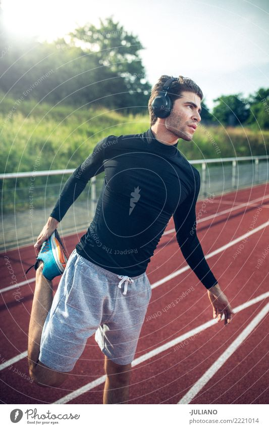 Young man doing stretching at runningtrack with headphones Drinking water Lifestyle Joy Body Healthy Healthy Eating Health care Athletic Muscular Fitness