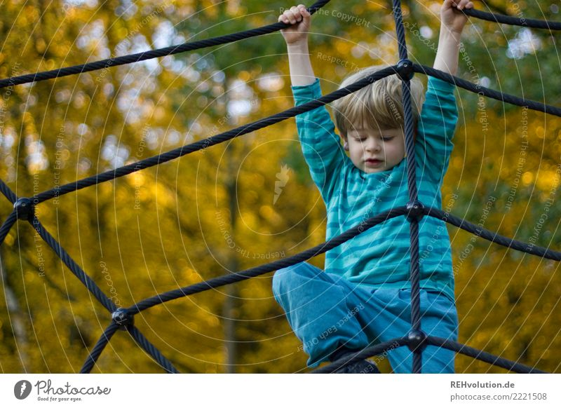 Child climbing on the playground in autumn Shallow depth of field blurriness Day Exterior shot Subdued colour Colour photo Climbing rope Rope Net Experience