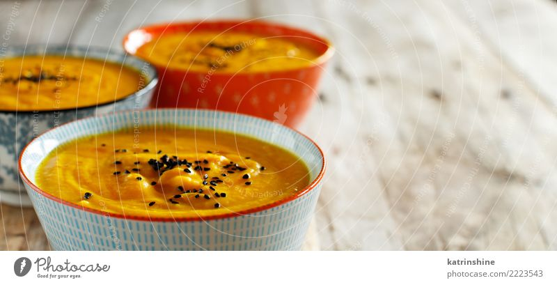 Fresh pumpkin soup in three bowls on a wooden table Vegetable Soup Stew Vegetarian diet Bowl Table Thanksgiving Hallowe'en Autumn Delicious Yellow Colour fall