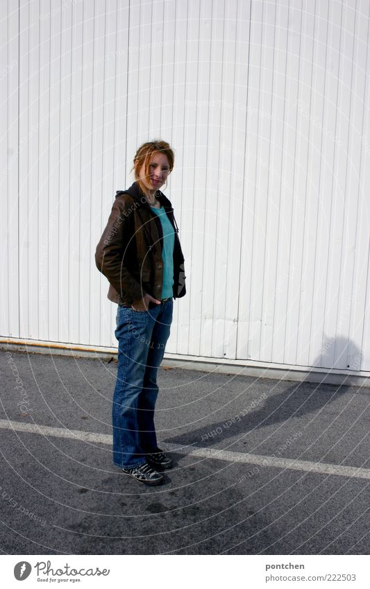 Young woman stands at the side of a white corrugated iron wall and casts shadows on the street and wall. Wait Youth (Young adults) Adults 1 Human being Jeans