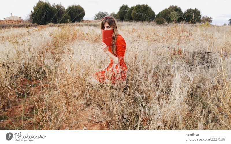 Young woman in a field with a red dress Lifestyle Style Harmonious Relaxation Human being Feminine Youth (Young adults) 1 18 - 30 years Adults Art Culture Book